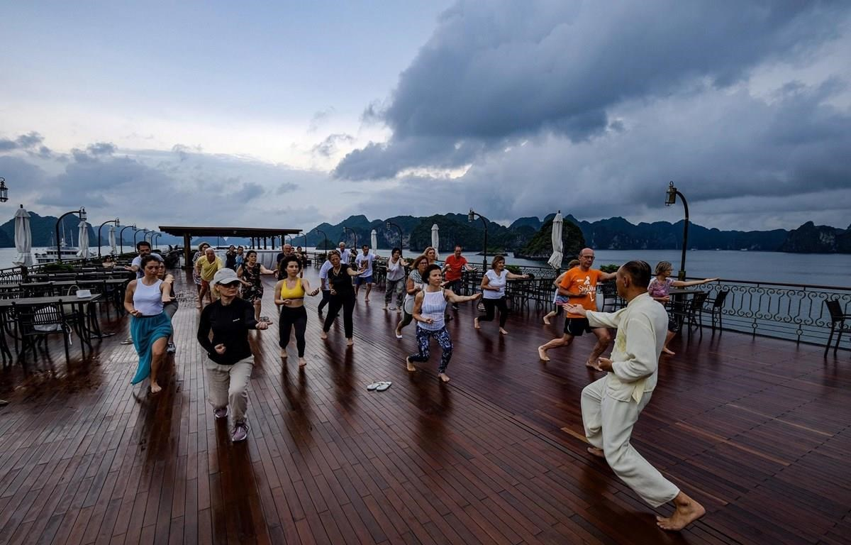 International tourists practice Tai chi aboard their cruise visiting Ha Long Bay. (Photo: VietnamPlus)