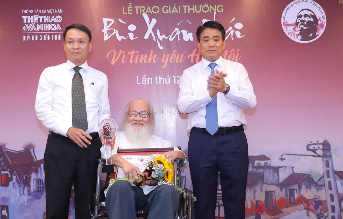 VNA Director General Nguyen Duc Loi (left) and Chairman of Hanoi People's Committee Nguyen Duc Chung present the Grand Prize to Associate Professor-Doctor-Emeritus Teacher Nguyen Thua Hy (centre) (Photo: courtesy of organizing board)