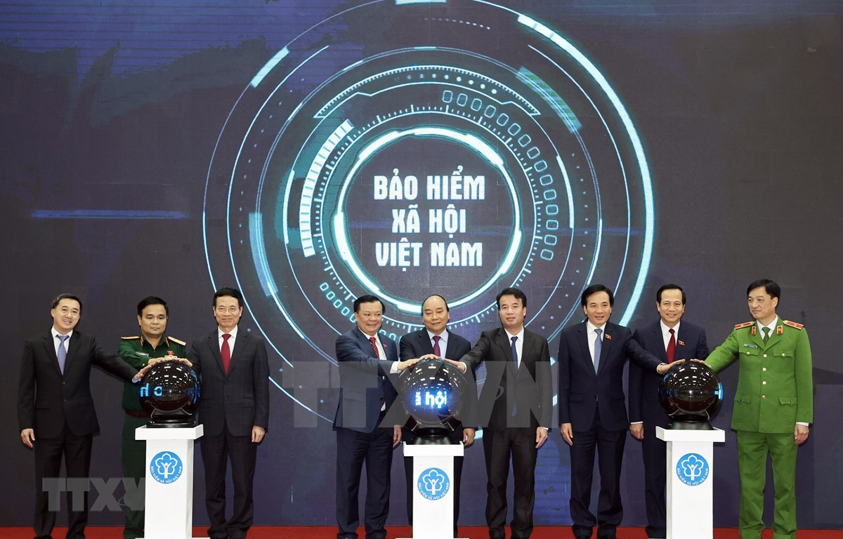 """Prime Minister Nguyen Xuan Phuc and other delegates press the button to launch the  """"VssID - Digital Social Insurance"""" application (Photo: VNA)"""