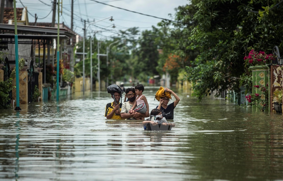 Residents evacuate their flooded homes in Gresik, East Java, Indonesia on December 15, 2020, as the rainy season brings floods to many areas in Jakarta and Java. (Photo: AFP/VNA)