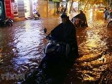 Hanoi residents wade through flood waters