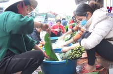 People cooking glutinous rice cakes for those in flood-hit areas