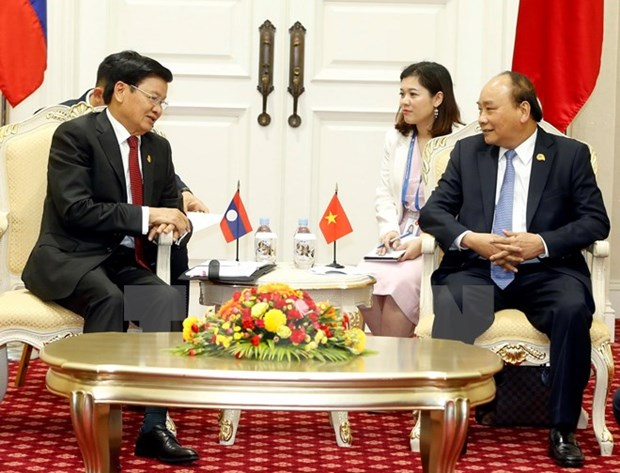 PM Nguyen Xuan Phuc meets Lao counterpart in Cambodia hinh anh 1
