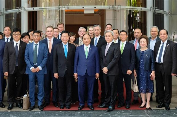 PM joins round-table discussion with international firms hinh anh 1