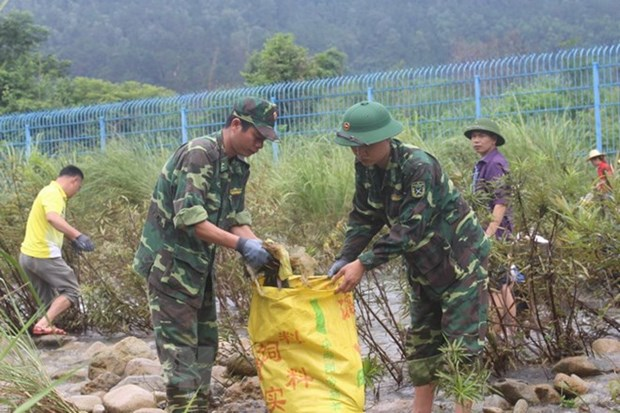 Vietnamese, Chinese people join hands to clean up border river hinh anh 1