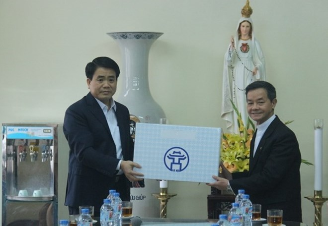 Chairman of the People's Committee Nguyen Duc Chung (L) presents a Tet gift to a representative of Thai Ha Parish (Photo: VNA)